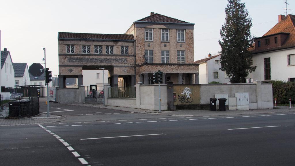 Der Portalbau eingerahmt von Mauern. Links die Zufahrt zu den neuen Häusern.